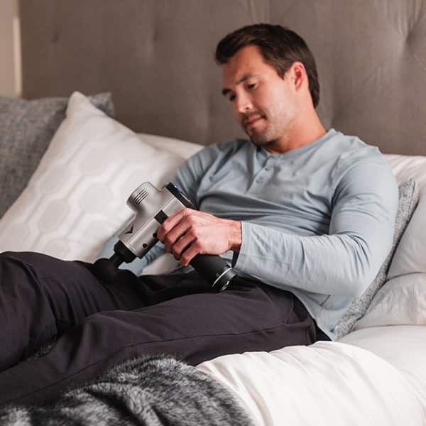 Man using hypervolt on bed